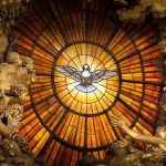 """A window of yellow alabaster is illuminated at its centre with an image of the Dove of the Holy Spirit. This is above the Cathedra Petri or """"Chair of St. Peter"""" altar at St. Peter's Basilica. The altar was created by Bernini. Bernini created a large b"""